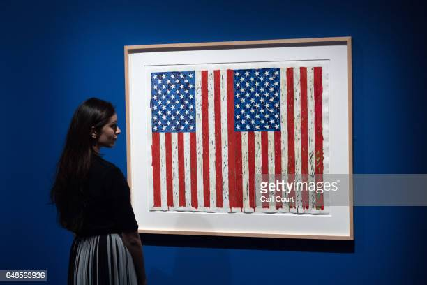 A member of staff poses for photographers next to a 1973 work by Jasper Johns entitled 'Flags I' during a press preview for the forthcoming...