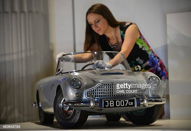 A member of staff poses for photographers with a miniature James Bond DB5 presented to Britain's Prince Andrew by the Aston Martin company in 1965 at...