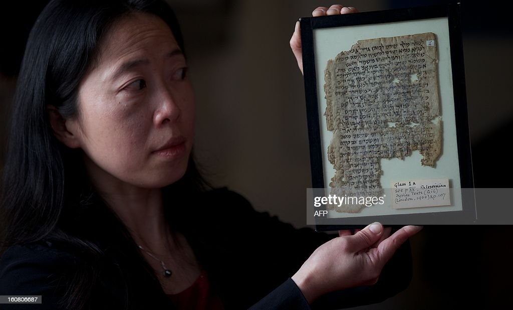 A member of staff poses holding the tractate 'Horayot' from the Jerusalem Talmud, part of the Lewis-Gibson Genizah Collection of manuscripts, at the British Academy in London on February 6, 2013. Oxford and Cambridge university have launched a joint fundraiser to purchase the Lewis-Gibson Genizah Collection which comprises of more than 1,700 fragments of Hebrew and Arabic manuscripts, originating from the Cairo Genizah and dating from the 9th - 19th century. The script on this page is a palimpsest, a reused parchment, with the 9th - 10th century text of the Jerusalem Talmud written over an earlier Christian work possibly dating from around 600 CE.