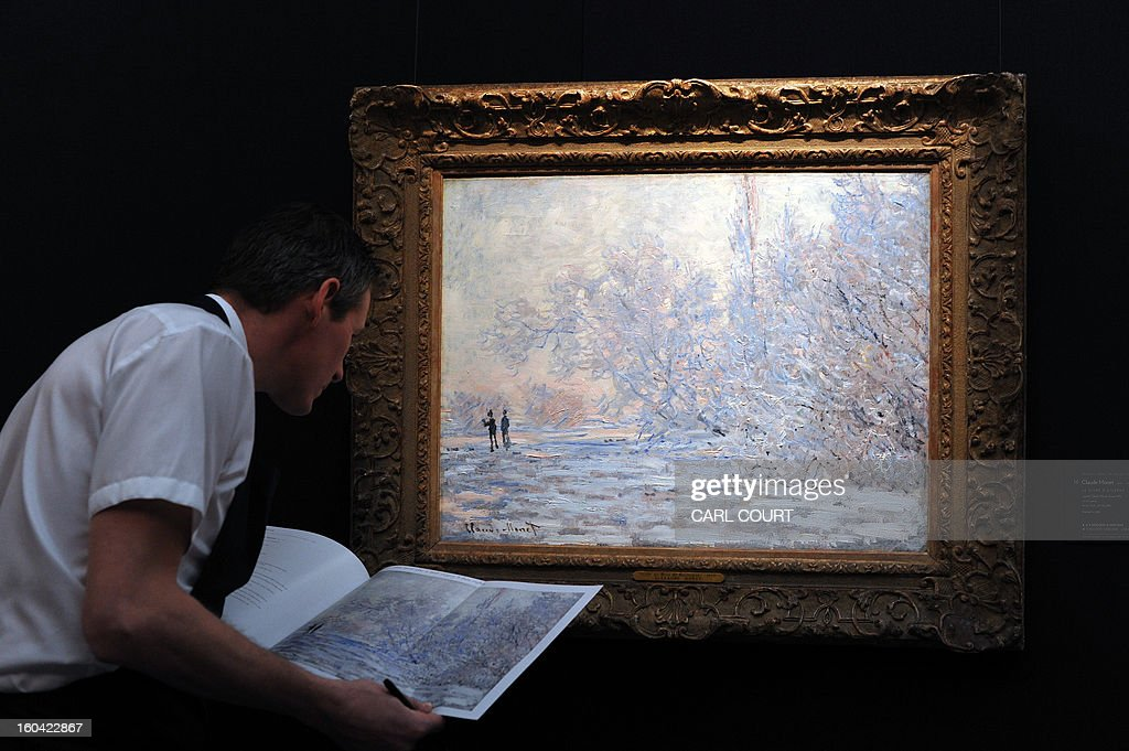 A member of staff poses next to a entitled 'Le Givre a Giverny' by French artist Claude Monet at Sotheby's auction house in central London on January 31, 2013. Due to form part of the Impressionist and Modern Art Evening Sale on February 5, it is expected to fetch between 4-6 million GBP (5-7 million EUR - 6-10 million USD). AFP PHOTO / CARL COURT