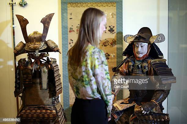A member of staff poses next to a figure of a samurai dressed in armour dating from around 1800 during a press preview for the Victoria and Albert...