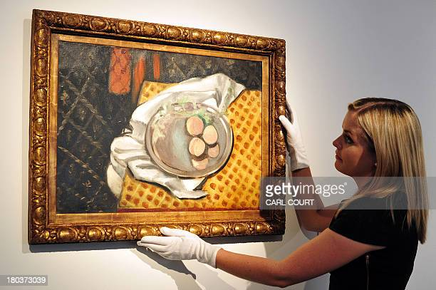 A member of staff poses next to a painting by French artist Henri Matisse entitled 'Peches' at Christies auction house in central London on September...