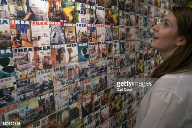 A member of staff poses next to a wall showing IKEA brochure covers over the last 30 years in the IKEA house on October 17 2017 in London England The...