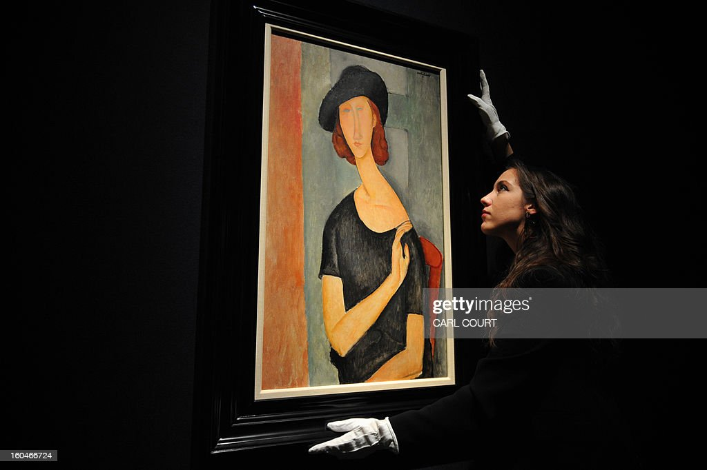 A member of staff poses next to a work entitled ''Jeanne Hebuterne (au chapeau)' by Italian artist Amedeo Modigliani at Christies auction house in central London on February 1, 2013. Due to form part of the Impressionist and Modern Art Evening Sale on February 6, it is expected to fetch between 16-22 million GBP (25-33 million USD - 18-25 million EUR).