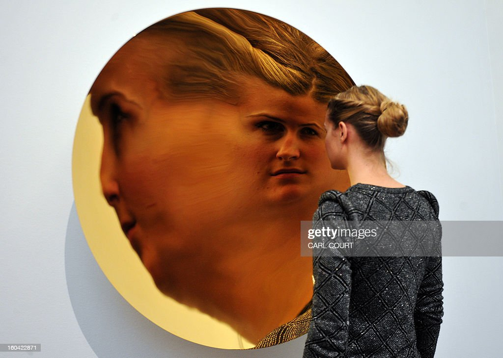 A member of staff poses next to a work entitled 'Untitled' by British artist Anish Kapoor in which her face is reflected at Sotheby's auction house in central London on January 31, 2013. Due to form part of the Contemporary Art Evening Sale on February 12, it is expected to fetch between 450,000-650,000 GBP (560,000-810,000 EUR - 725,000-1,050,000 USD).