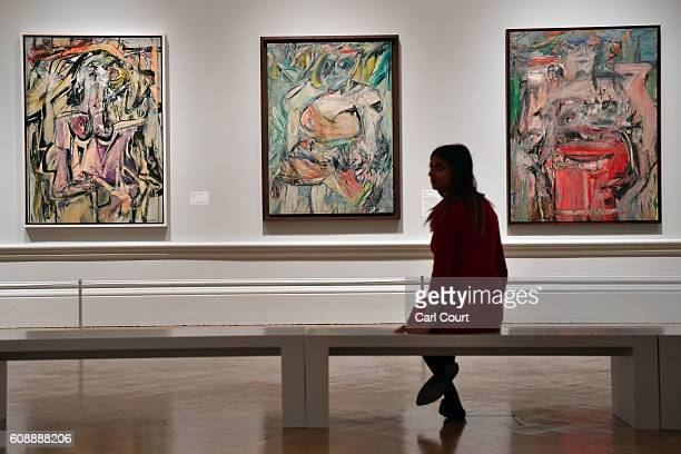 A member of staff poses next to paintings by Dutch American artist Willem de Kooning entitled 'Woman' 'Woman II' and 'Woman as Landscape' at the...