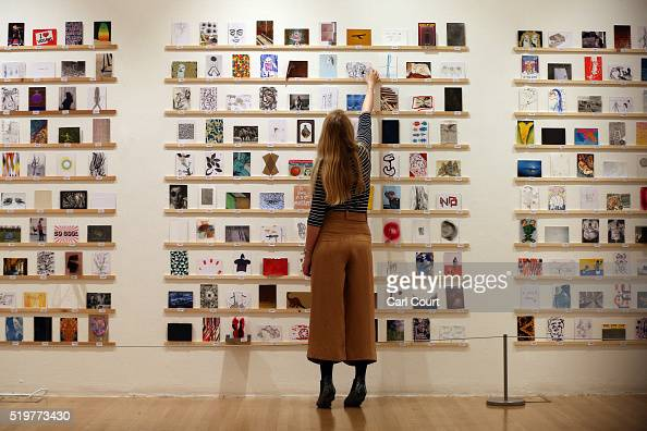 A member of staff poses next to postcards at the RCA secret postcard art sale at the Royal College of Art on April 8 2016 in London England The...