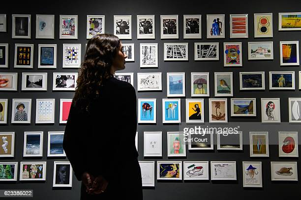 A member of staff poses next to some of the 400 postcards by various artists including Damien Hirst and Grayson Perry on display ahead of a secret...