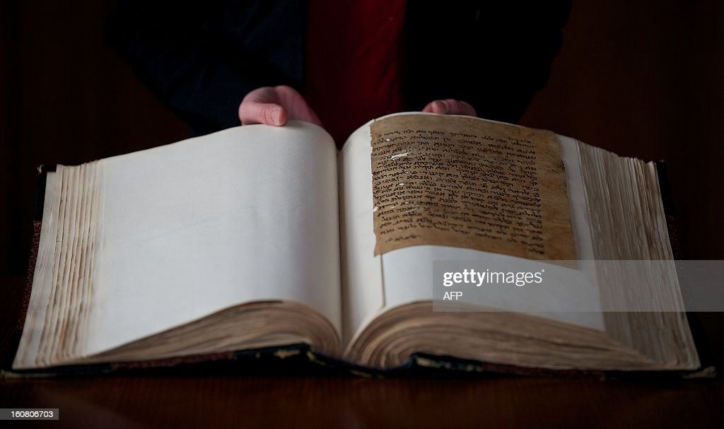 A member of staff poses with a 12th - 14th century text in which a Jewish woman pleads with her husband to return home, part of the Lewis-Gibson Genizah Collection of manuscripts, at the British Academy in London on February 6, 2013. Oxford and Cambridge university have launched a joint fundraiser to purchase the Lewis-Gibson Genizah Collection which comprises of more than 1,700 fragments of Hebrew and Arabic manuscripts, originating from the Cairo Genizah and dating from the 9th - 19th century.