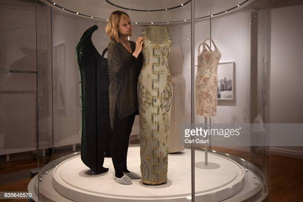 A member of staff poses with a 1991 Versace iceblue silk gown with beading worn for a Harper's Bazaar photoshoot during a preview for the forthcoming...