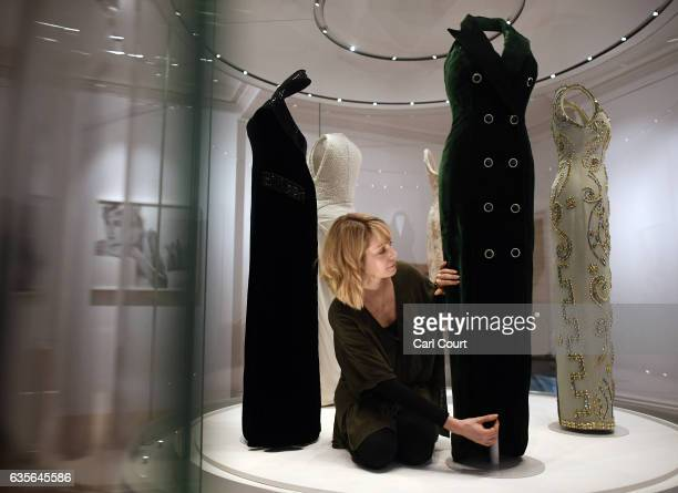 A member of staff poses with a 1992 Catherine Walker green silk velvet evening dress with velvet and diamante buttons worn for Diana's Vanity Fair...