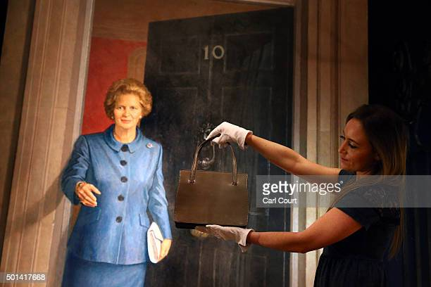 A member of staff poses with a 'Grey Leather Handbag' during a press preview at Christies auction house on December 15 2015 in London England Due to...