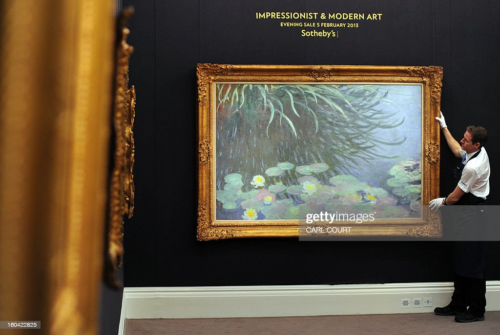 A member of staff poses with a painting entitled 'Nympheas avec reflets de hautes herbes' by French artist Claude Monet at Sotheby's auction house in central London on January 31, 2013. Due to form part of the Impressionist and Modern Art Evening Sale on February 5, it is expected to fetch between 12-18 million GBP (15-22 million EUR - 19-29 million USD).
