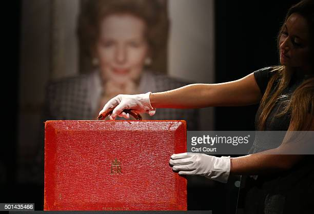 A member of staff poses with a 'Prime Ministerial Red Morocco Dispatch Box' during a press preview at Christies auction house on December 15 2015 in...