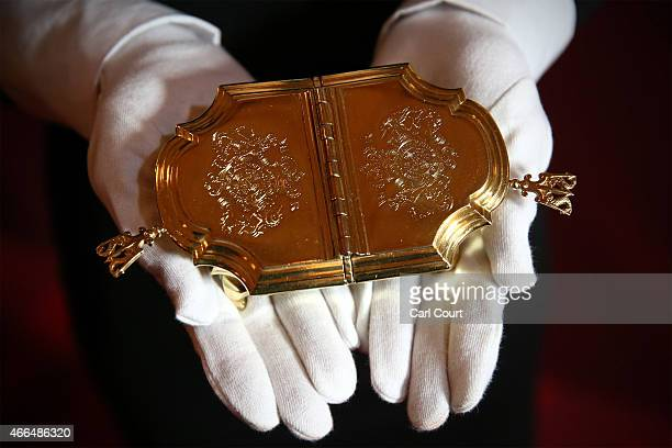 A member of staff poses with a salt cellar from 1721 containing two compartments for salt and mustard during a photocall to showcase items from the...