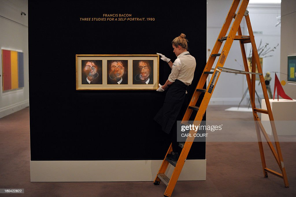 A member of staff poses with a triptych painting entitled 'Three Studies for a Self-Portrait' by British artist Francis Bacon at Sotheby's auction house in central London on January 31, 2013. Due to form part of the Contemporary Art Evening Sale on February 12, it is expected to fetch between 10-15 million GBP (12-18 million EUR - 16-24 million USD).