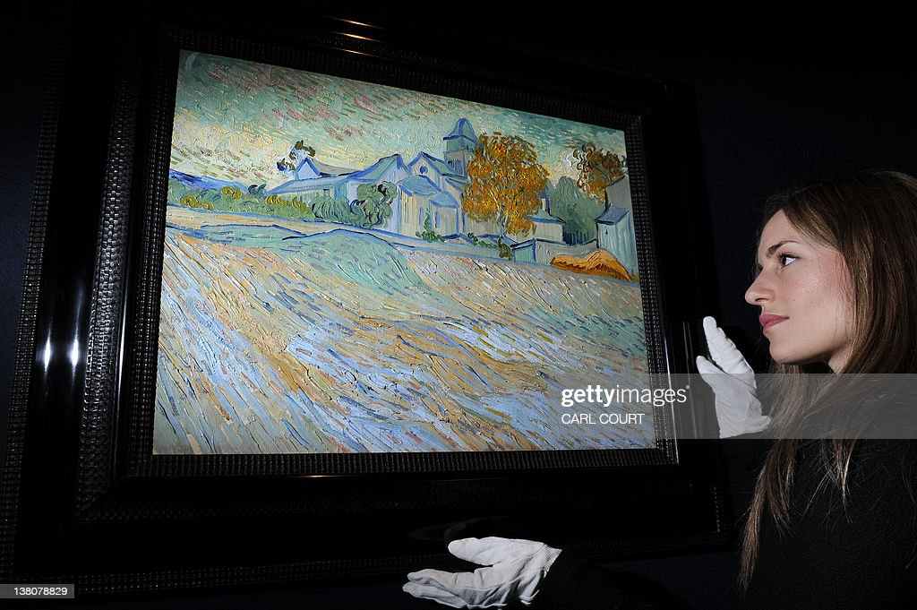 A member of staff poses with an 1889 painting by Dutch painter Vincent Van Gogh entitled 'Vue de l'Asile et de la Chapelle de Saint-Remy' during a press preview prior to the 'Impressionist and Modern Art Sale' at Christie's auction house in central London on February 2, 2012. From the collection of late actress Elizabeth Taylor, it will come under the hammer on February 7, 2012 and is expected to fetch between 5 - 7million British pounds (7.6 - 11 million US dollars, 5.7 - 7.9 million euros).