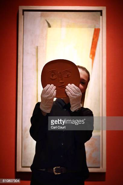 A member of staff poses with an unglazed terracotta plate entitled 'Visage aux grands yeux' by Pablo Picasso in front of a painting by Ben Nicholson...