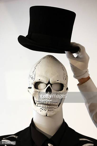 A member of staff poses with the hat and mask from James Bond's Day of the Dead Costume worn by Daniel Craig in Spectre during a photocall at...