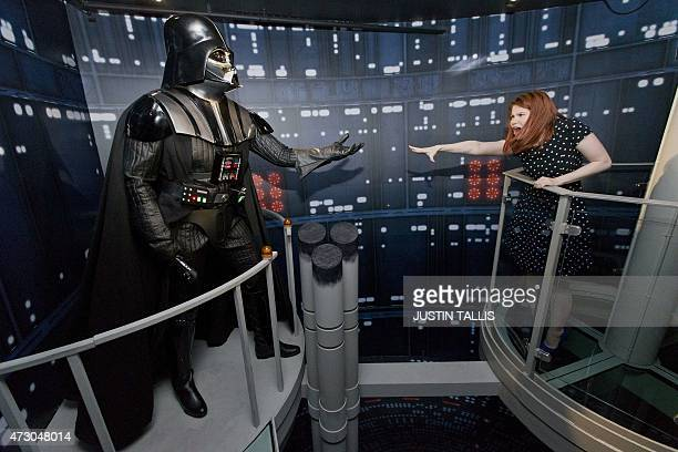 A member of staff poses with the wax figure of Star Wars character Darth Vader at the Star Wars At Madame Tussauds attraction in London on May 12...