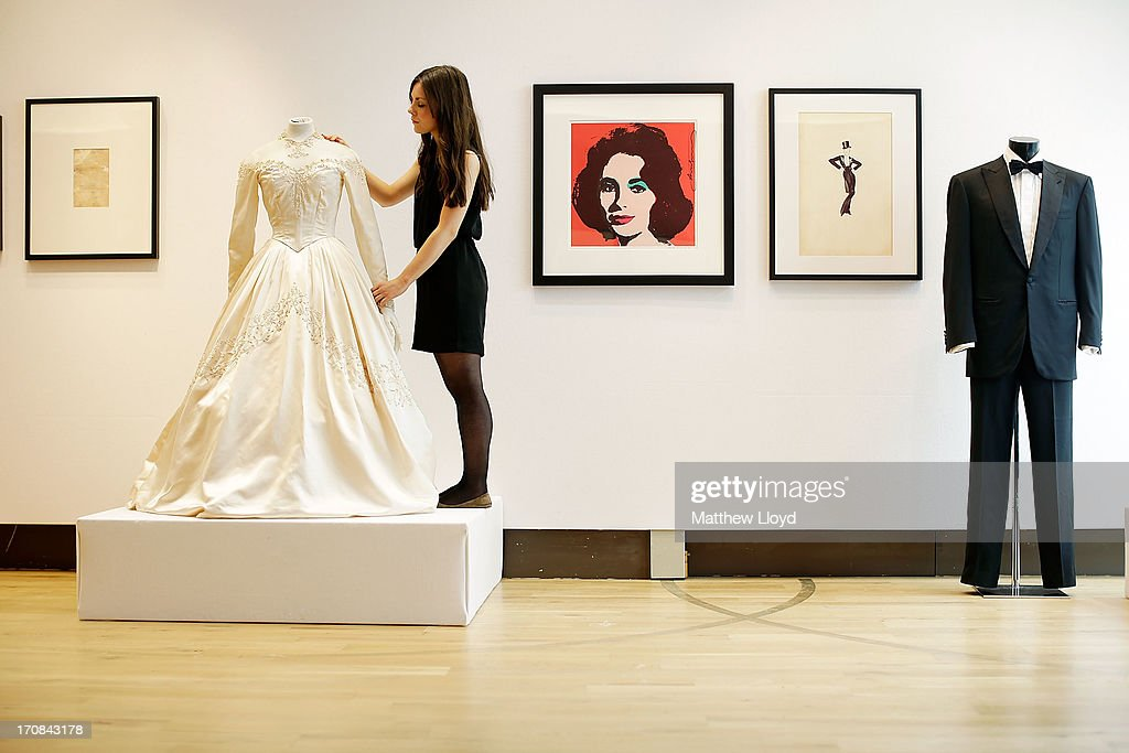 A member of staff prepares a dress, worn by Elizabeth Taylor for her first wedding in 1950, for sale at Christie's South Kensington on June 19, 2013 in London, England. The item is part of an auction entitled 'Pop Culture' featuring memorabilia charting the history of cinema, pop and rock and roll.