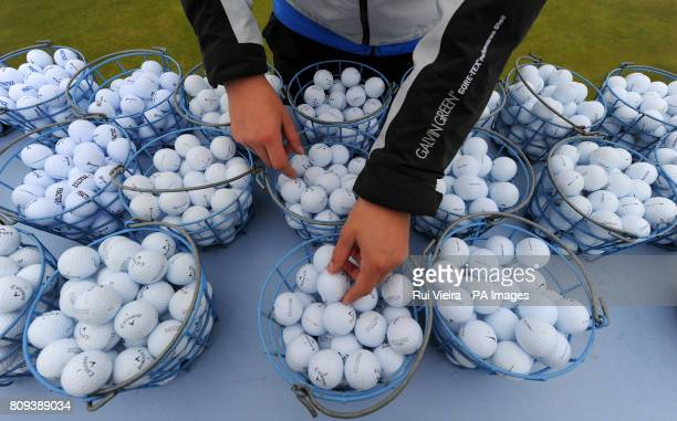 A member of staff puts out buckets of golf balls on a table on the practice green in preparation for round three of the 2011 Open Championship at...