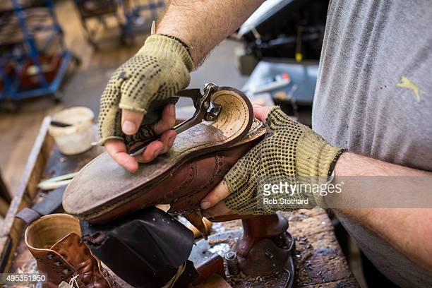 A member of staff removes the sole of a shoe sent in for repair at the Joseph Cheaney and Sons factory on August 25 2015 in Desborough United Kingdom...