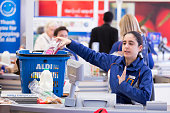 A member of staff scans goods taken from a customer's shopping basket at the checkout counter inside an Aldi supermarket store in London UK on Monday...