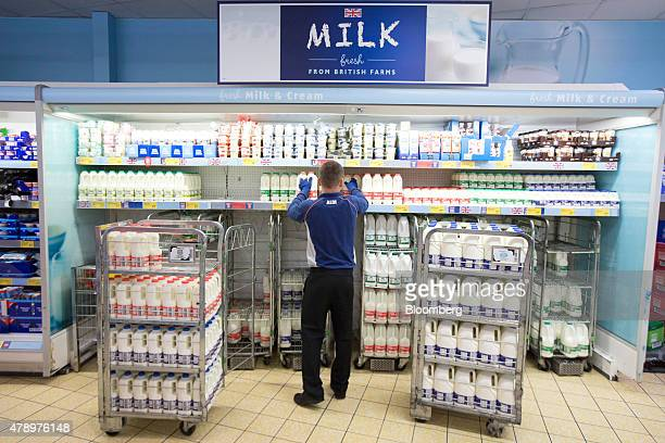 A member of staff stacks the milk and cream counter with bottles of skimmed semiskimmed and whole milk inside an Aldi supermarket store in London UK...
