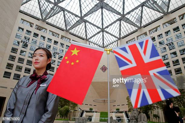 A member of staff stands behind flags as officials arrive for the UKChina High Level Financial Services Roundtable at the Bank of China head office...