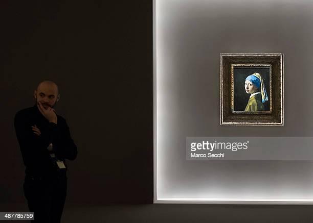 A member of staff stands next to Vermeer's 'La ragazza con l'orecchino di perla' at Palazzo Fava on February 8 2014 in Bologna Italy The exhibition...