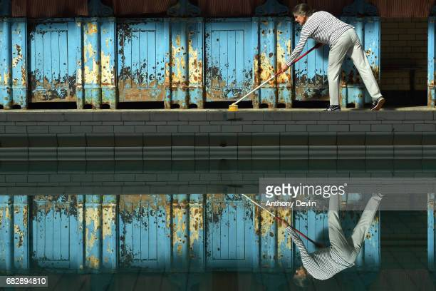 A member of staff sweeps the pool side of the Men's First Class pool at Victoria Baths which are opening today for the first time in over 20 years...