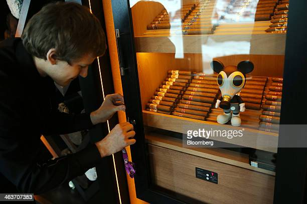 A member of staff unlocks the cigar cabinet in the 'Studio Grigio' bar at the InterContinental hotel Davos operated by InterContinental Hotels Group...