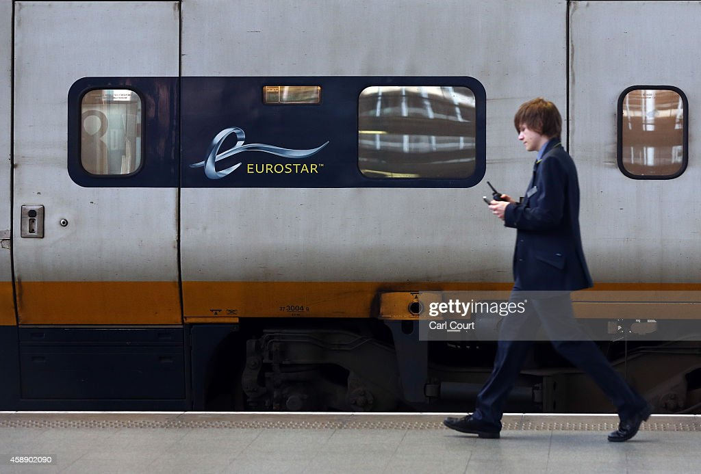 A member of staff walks alongside an old Eurostar train during a press preview of Eurostar's new e320 train at St Pancras Station on November 13 2014...