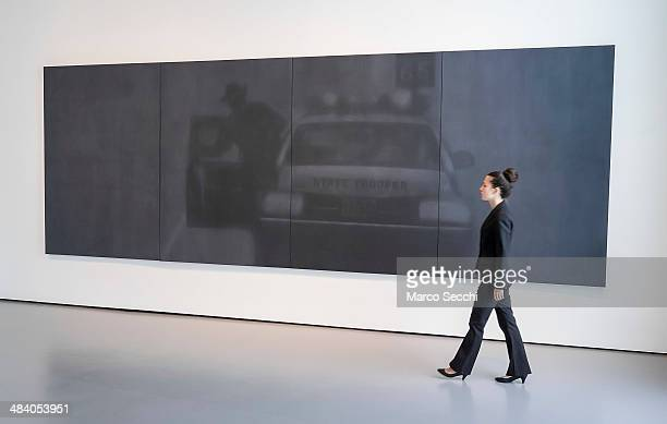 A member of staff walks in front of one of the photographs by Irving Penn during the press preview of the new exhibition at Palazzo Grassi on April...