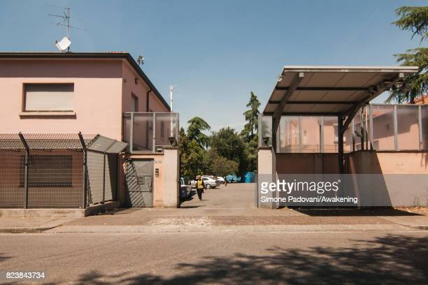 A member of staff walks to the offices at the entrance of Hub CARA on July 27 2017 in Bologna Italy In an effort to address the overcrowding violence...