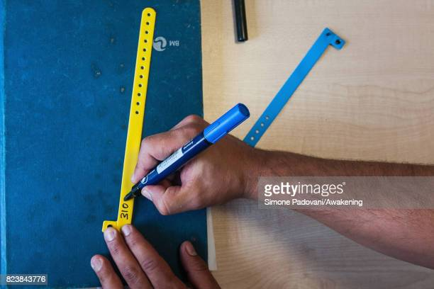 A member of staff writes the code number assigned to an asylum seeker on a wrist band This is to check the presences of the asylum seeker every day...