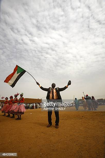 A member of Sudan's Nuba community waves the Sudanese flag as he takes part in the Nuba Mountains Cultural Heritage Festival marking the...