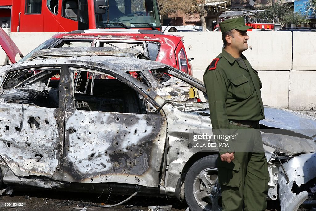 A member of Syrian security forces stands guard next to a damaged vehicle at the site of a suicide attack at a police officer's club in the Masaken Barzeh district of the capital Damascus on February 9, 2016. The Syrian Observatory for Human Rights said about 20 people had also been wounded, adding that policemen were among the dead and injured. BESHARA