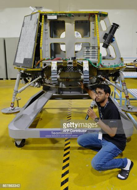 A member of 'Team Indus' explains technical aspects of a spacecraft that will carry the team's unmanned rovers to the moon during a demonstration to...