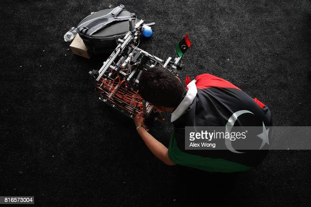 A member of Team Libya works on his team's robot during the first of two days of the First Global International Robot Olympics an international...