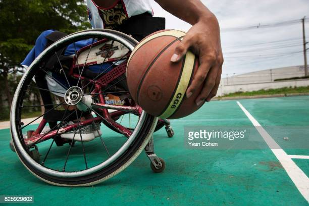 A member of Thailand national wheelchair basketball team holds a basketball at a government sports facility in Cholburi province about an hour and a...