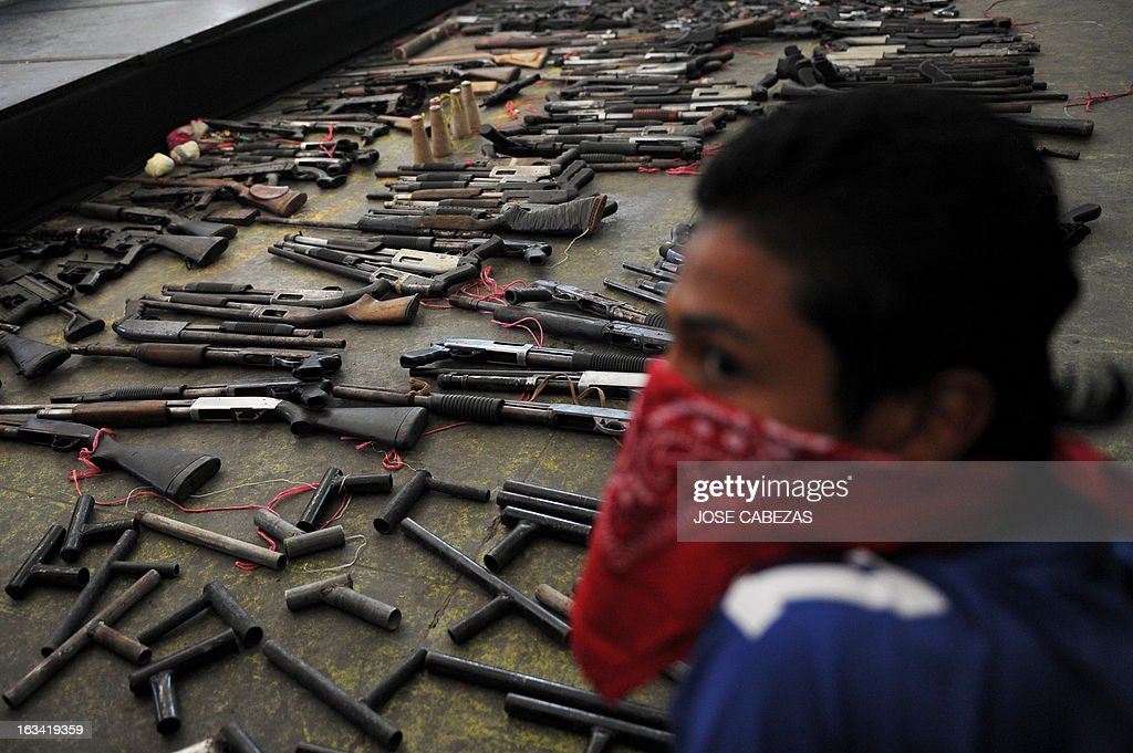 A member of the '18 street' gang takes part in an event to hand in weapons in Apopa, 14 Km north of San Salvador, El Salvador on March 9, 2013. Gang leaders surrendered about 267 weapons as part of the truce process between gangs in El Salvador. AFP PHOTO/ Jose CABEZAS