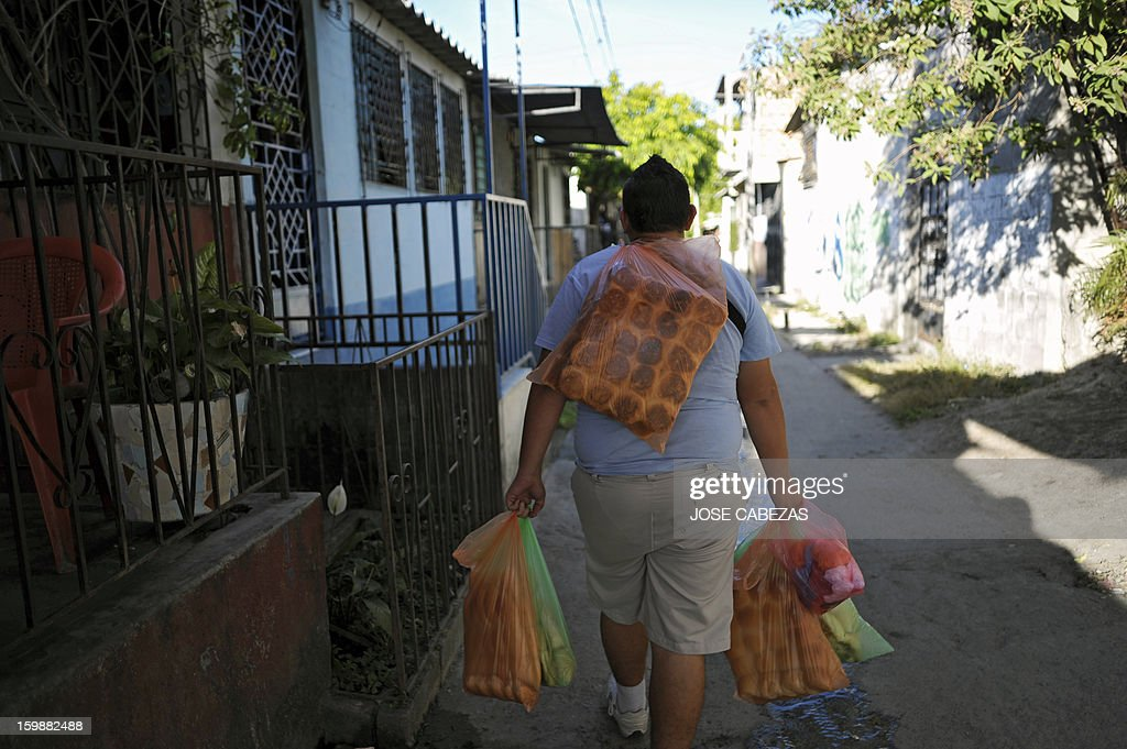 A member of the 18th street gang holds bags with bread for sale from a bakery operated by gang members as a part of a rehabilitation program in San Bartolo neigbourhood, in Ilopango, a suburb of San Salvador on January 21, 2012. Gang leaders started the second phase of the gang truce to reduce crime in El Salvador. AFP PHOTO/ Jose CABEZAS