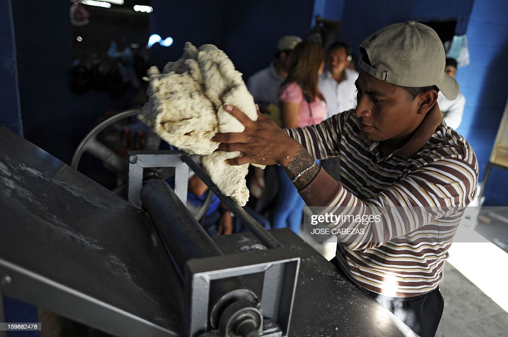 A member of the 18th street gang prepares dough at a bakery operated by gang members as a part of a rehabilitation program in San Bartolo neigbourhood, in Ilopango, a suburb of San Salvador on January 21, 2012. Gang leaders started the second phase of the gang truce to reduce crime in El Salvador. AFP PHOTO/ Jose CABEZAS