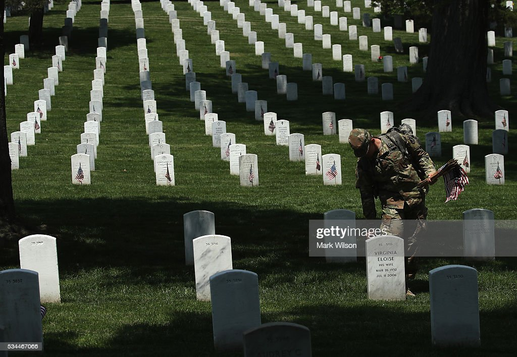 A member of the 3rd U.S. Infantry Regiment, 'The Old Guard,' places a flag at a grave site during the 'Flags-In' ceremony May 26, 2016 at Arlington National Cemetery in Arlington, Virginia. A small American flag was placed one foot in front of more than 220,000 graves in the cemetery to mark Memorial Day.
