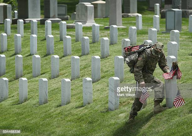 A member of the 3rd US Infantry Regiment 'The Old Guard' places a flag at a grave site during the 'FlagsIn' ceremony May 26 2016 at Arlington...