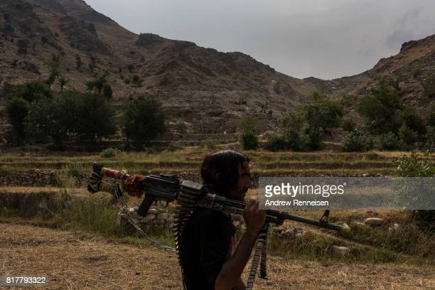 A member of the Afghan Local Police walks past the area where the United States dropped the GBU43/B Massive Ordnance Air Blast nicknamed the 'Mother...