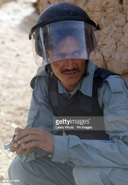 A member of the Afghan National Police holds a hand grenade outside a compound as he takes part in Operation Yaklang in Helmand Province Afghanistan