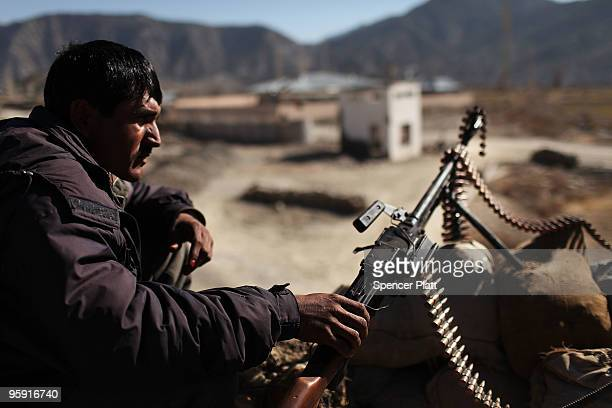 A member of the Afghan National Police keeps watch outside of the district center beside Combat Outpost Zerak on January 21 2010 in Zerak Afghanistan...